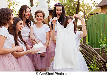 Suprised bride takes gift from friends. Hen-party celebration