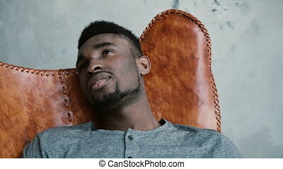 sur, séance, cuir, africaine, jeune, pensée, sourire., regarde, chaise, portrait, mâle, thoughtfully., quelque chose, homme