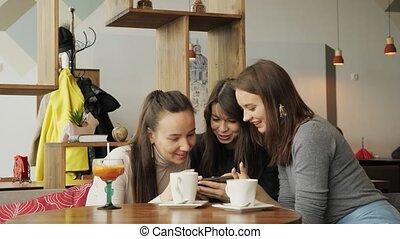 sur, séance femme, il, petites amies, trois, regarder, conversation, smartphone, quelque chose, cafe.