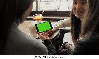 sur, smartphone, séance, écran, il, petites amies, regarder, conversation, vert, cafe., femmes