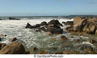 Surf at rocky ocean coast.