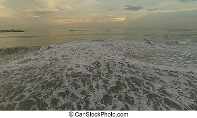 Surf at sunset - Aerial view of unidenfied people surfing at...