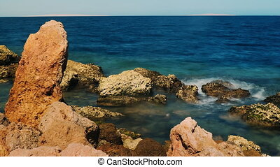 Surf at the rocks - Red stone on a background of blue sea