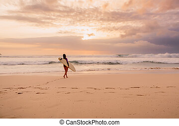 Surf girl go to ocean for surfing. Surfer woman on a beach at sunset
