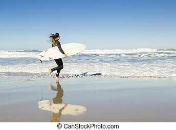 Surf girl - Teenager girl in the beach with her surfboard