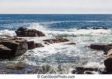 Surf Hitting Rocks in Blue Water