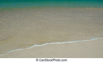Surf on a tropical beach with yellow sand