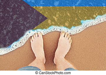 Surf on sandy beach with flag Bahamas. top view