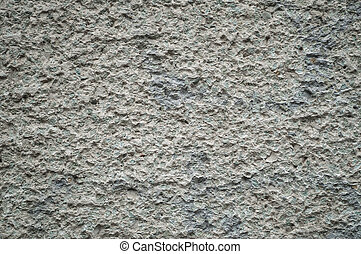 Surface texture of gray stone hewn wall.