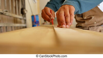 Surfboard maker measuring surfboard 4k - Close up of...