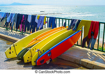 Surfboards and wetsuits at beach