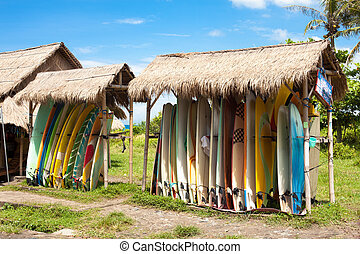 Surfboards in rack for rent on beach in Bali