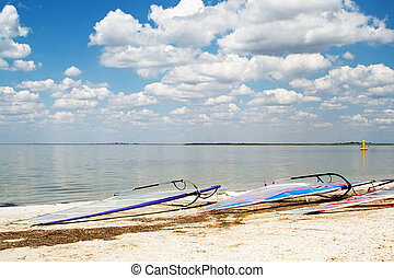 Surfboards on a beach a sea bay on background of the blue sky and clouds