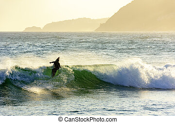 Surfer and wave silhouette at sunset