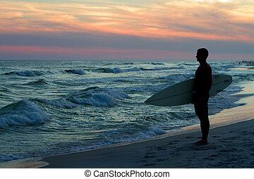 Surfer At Sunset - Surfer stands at the coastline holding...