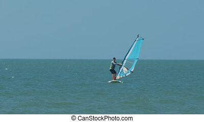 Surfer Beginner Sails in Azure Sea under Sunlight - surfer...