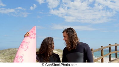 Surfer couple with surfboard looking each other at beach 4k