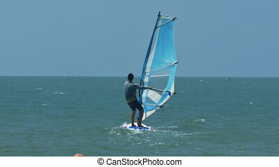 Surfer Fights with Wind Tries Hold Sail at Ocean - close...