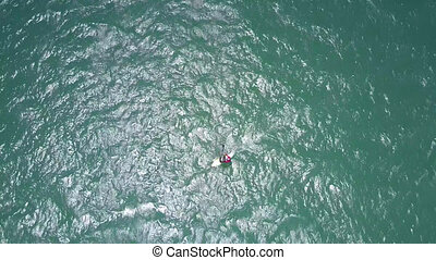 surfer follows rippling azure ocean waves - view from drone...