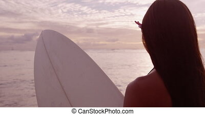 Surfer girl going surfing looking at ocean beach sunrise. Beautiful woman looking at water standing with surfboard having fun living healthy active lifestyle. RED EPIC SLOW MOTION.