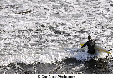 Surfer heading out to sea