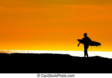 Surfer heading along the cliffs at Santa Cruz for the Pacific Ocean, to get in one more ride before sunset