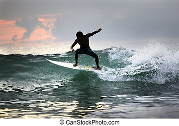Surfer in ocean on sunset. Bali. Indonesia