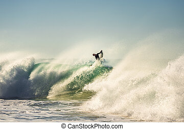 Surfer jumping a powerful and big wave at sunset