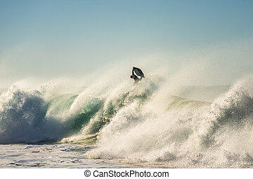 Surfer jumps a powerful and big wave at sunset
