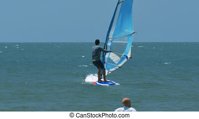 Surfer Lifts Sail by Mast Bald Instructor Watches - close...