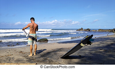 Surfer man stands on sandy beach