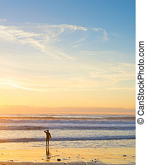 Surfer ocean beach sunset background
