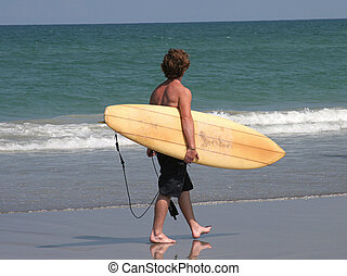 Surfer on Beach - a young man walking along the beach with...