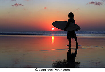 Surfer on sunset - Silhouette of surfer at red sunset. Kuta...
