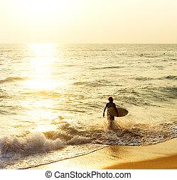 Surfer on the ocean beach at sunset in Hikkaduwa, Sri Lanka