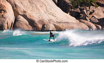 Surfer on the waves - Young male surfer on the clear blue ...