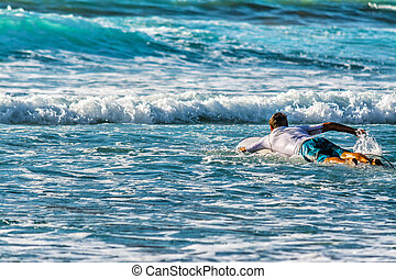 Surfer paddling to the line up