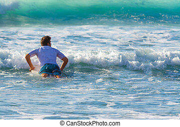 Surfer paddling to the lineup on a sunny day