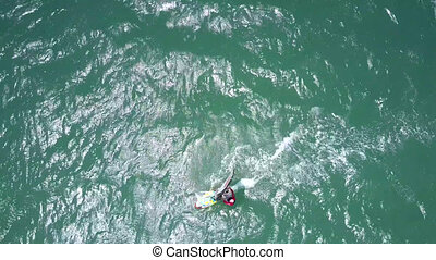 surfer rides gleaming azure ocean waves - view from flycam...