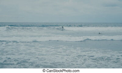 surfer rides Ocean Waves at beach at Bali in Slow Motion
