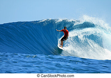 Surfer in red shirt enjoying speed on a perfect wave