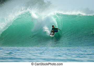 Surfer riding fast on tropical green wave, Indonesia -...