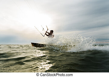 Surfer splashing in front of the sun