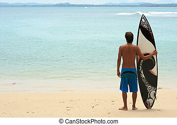 Surfer standing on beach with funky arty surfboard - ...