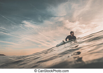 Surfer waiting for a big wave at sunset
