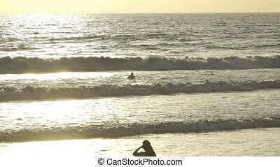 Surfer waiting wave in ocean at sunset in slow motion -...