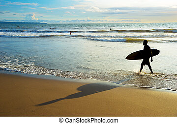 Surfer walk out ocean silhouette
