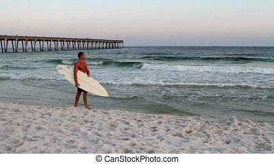 Surfer Walking Beach - Male surfer wearing a swim suit and...