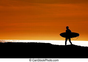 Surfer walking to the ocean for a sunset ride