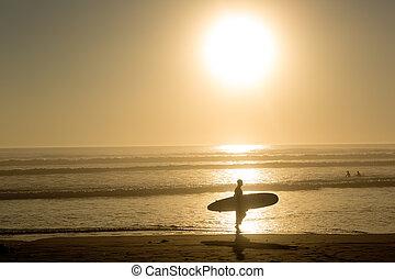 surfer walks in the sunset